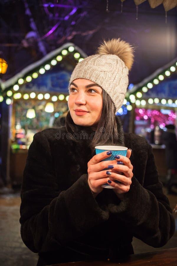 Ein schönes junges Mädchen trinkt heißen Tee am Weihnachtsmarkt Konzept-Lebensstil, städtisch, Winter, Ferien lizenzfreie stockbilder