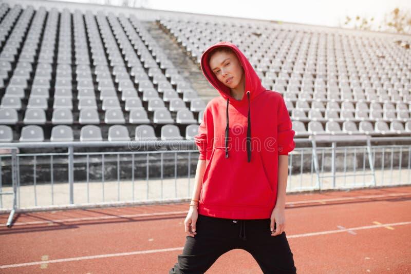 Ein schönes junges Mädchen von Mischrasseständen auf einer Sportstadionslaufbahn kleidete in einem roten Hoodie mit einer Haube a lizenzfreie stockfotografie