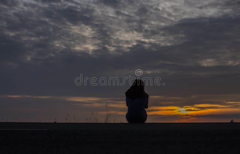 Ein schönes junges Mädchen zeigt den Sonnenuntergang im Wasser stockfoto