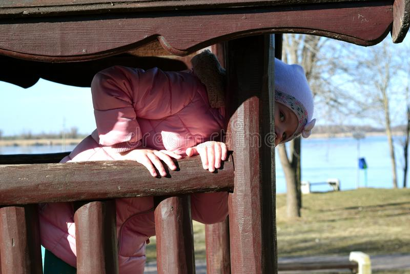 Ein schönes kaukasisches glückliches Mädchenkind, das draußen aus dem Fenster des Holzhauses im Park heraus lacht und schaut 4 Ja lizenzfreie stockfotografie
