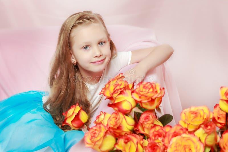 Ein schönes kleines Mädchen mit lang, Licht, gelocktes Haar, in einem Blau lizenzfreie stockfotos