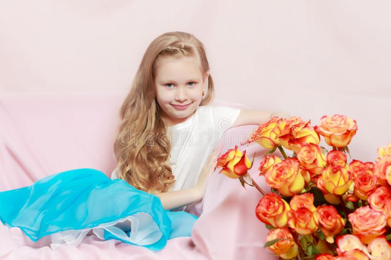 Ein schönes kleines Mädchen mit lang, Licht, gelocktes Haar, in einem Blau lizenzfreies stockfoto