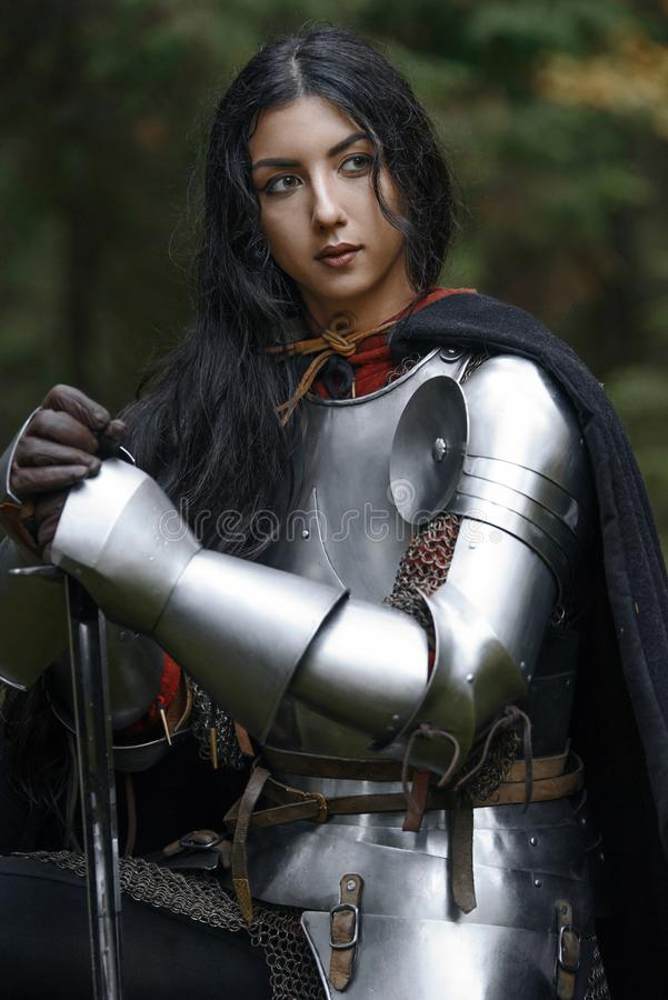 Ein schönes Kriegersmädchen mit einem Klinge tragenden chainmail und Rüstung in einem mysteriösen Wald stockbild