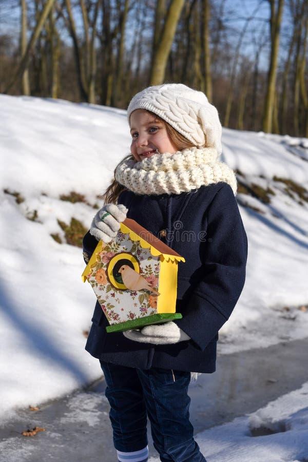 Ein schönes lächelndes kleines Mädchen, das ein Vogelhaus in einem Park hält lizenzfreie stockfotografie