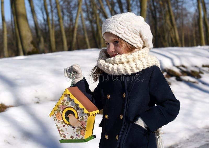 Ein schönes lächelndes kleines Mädchen, das ein Vogelhaus in einem Park hält stockbild