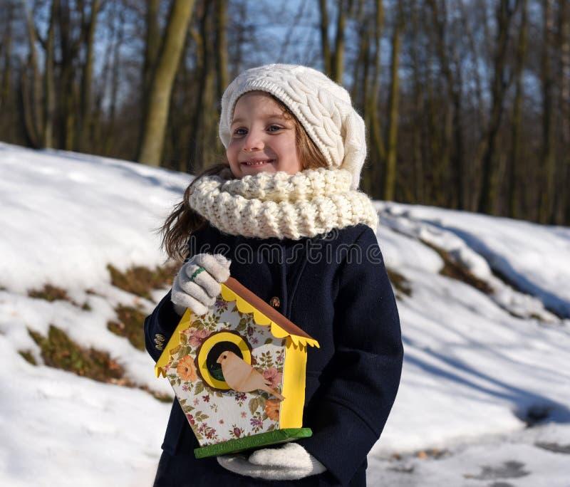 Ein schönes lächelndes kleines Mädchen, das ein Vogelhaus in einem Park hält lizenzfreies stockfoto
