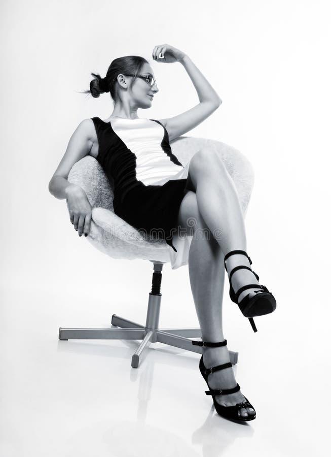 Ein schönes Mädchen, das auf einem Stuhl sitzt stockfotografie