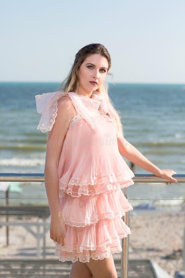 Ein schönes Mädchen, das auf einem transparenten Balkon auf einem blauen Seehintergrund aufwirft Eine Dame in einem rosa Kleid mi stockfotografie