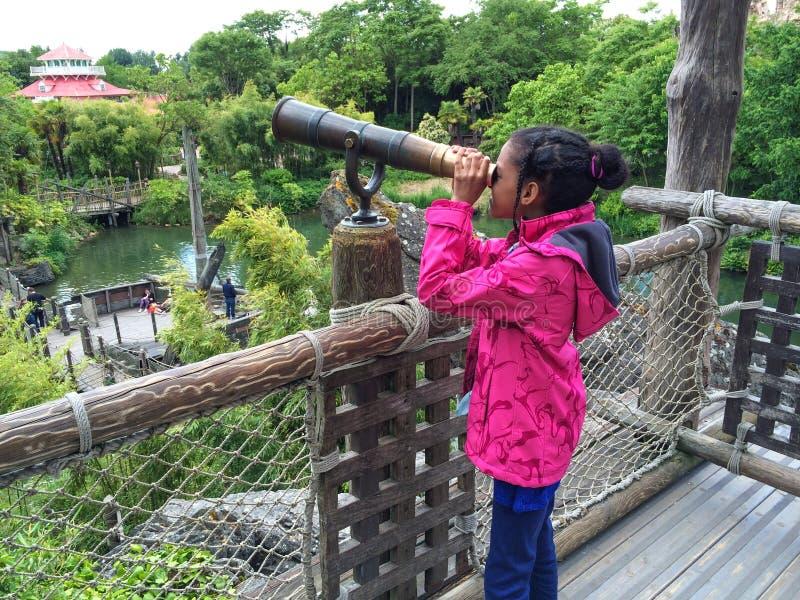 Ein schönes Mädchen, das durch ein Teleskop dem Park betrachtet lizenzfreie stockfotos