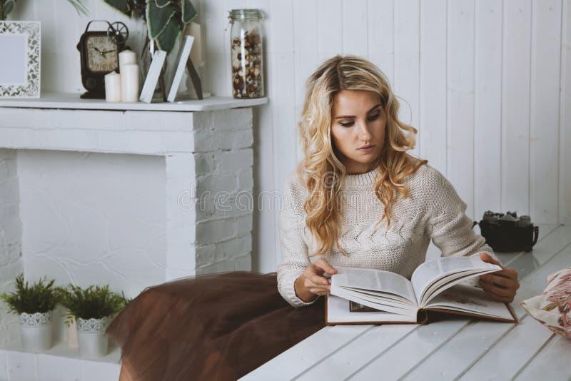 Ein schönes Mädchen, das nachdenklich ein Buch liest lizenzfreies stockfoto
