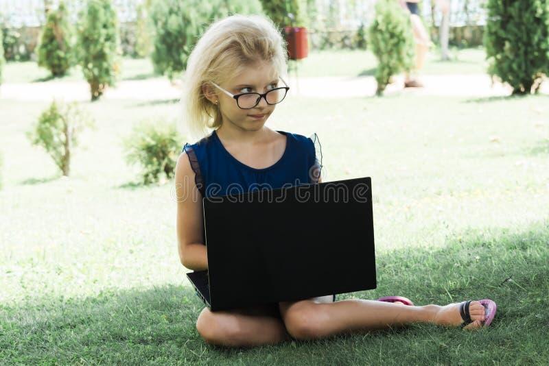Ein schönes Mädchen in den Gläsern arbeitet an einer Berechnung, draußen Der Student macht Lektionen auf einem Laptop stockfotografie