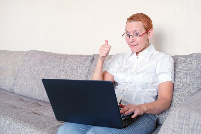 Ein schönes Mädchen in den Gläsern mit rote Rahmenkonstruktionen am Laptop Gefühl der Freude mit der Geste eines erfolgreichen Ge lizenzfreies stockbild