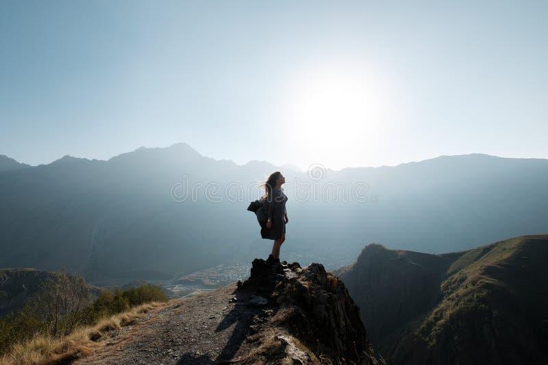 Ein schönes Mädchen in einem Fliegenkleid sitzt auf einer Klippe, welche die Berge übersieht lizenzfreies stockfoto