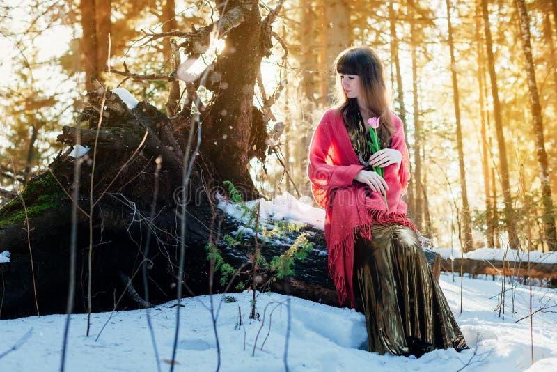 Ein schönes Mädchen in einem Goldkleid sitzt in einem sonnigen Wald des Frühlinges mit einer Tulpe in ihren Händen lizenzfreie stockbilder