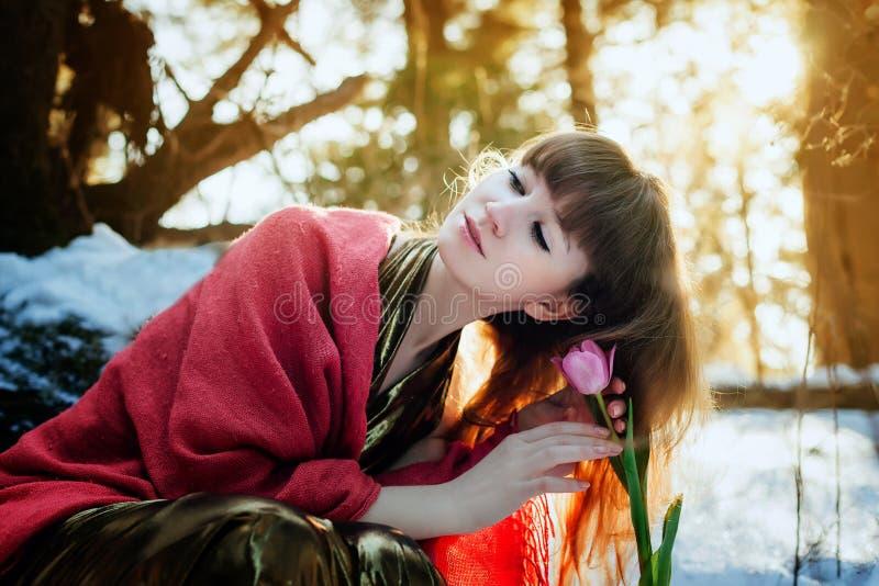 Ein schönes Mädchen in einem Goldkleid sitzt in einem sonnigen Wald des Frühlinges und berührt eine Tulpe stockbild