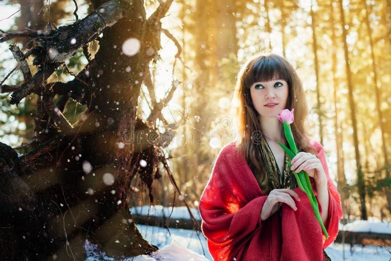 Ein schönes Mädchen in einem Goldkleid steht in einem sonnigen Wald des Frühlinges mit einer Tulpe in ihren Händen stockbild
