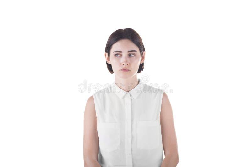 Ein schönes Mädchen ist das Leiden, lokalisiert auf einem weißen Hintergrund Die traurige und ernste Frau schaut weg stockfotos