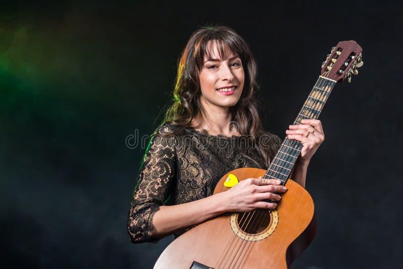 Ein schönes Mädchen mit dem dunklen Haar hält eine Gitarre auf einem rauchigen Hintergrund Grün-blaue Beleuchtung lizenzfreie stockfotos