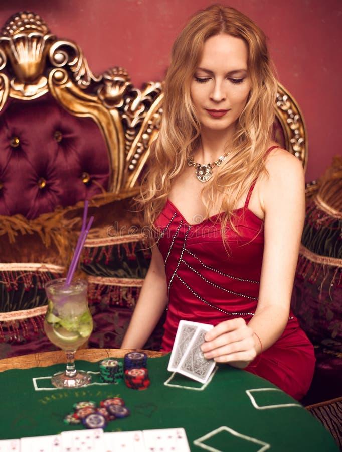 Ein schönes Mädchen sitzt auf einer Couch, die Schürhaken auf grünem Stoff spielt und hält Spielkarten in ihren Händen lizenzfreie stockfotos