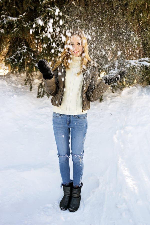 Ein schönes Mädchen wirft Schnee mit ihren Händen stockfoto