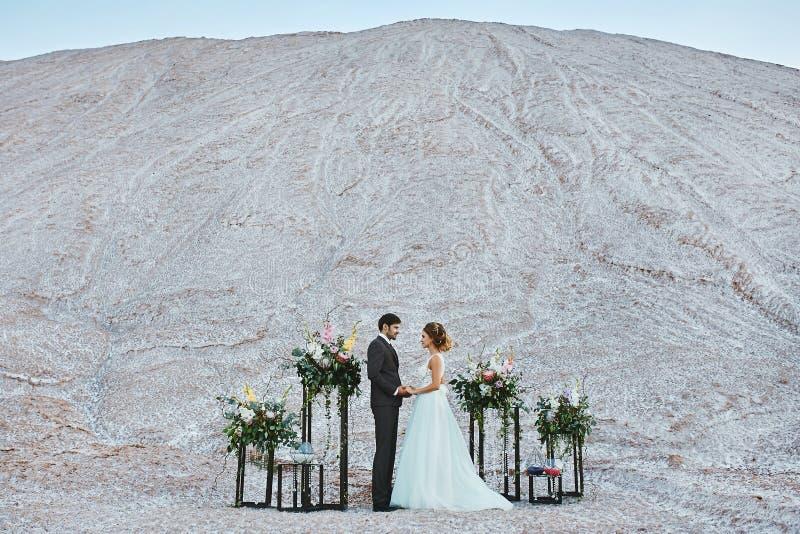 Ein schönes Paar von Liebhabern an einer weißen Wüste, eine junge Frau mit einer Heiratsfrisur in einem stilvollen Kleid und ein  stockfotografie