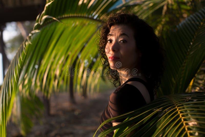 Ein schönes Porträt der jungen Frau unter den Blättern von Palmen lizenzfreie stockfotografie