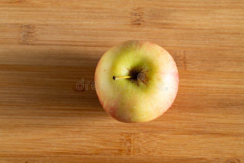 Ein schönes rotes gelbes Apple auf einem hölzernen Hintergrund stockfoto