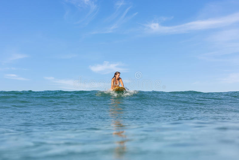 Ein schönes sportliches Mädchen, das in den Ozean surft lizenzfreies stockfoto