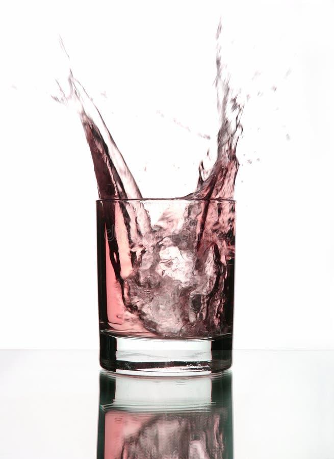 Ein schönes Spritzen des Eises in einem Glas rosafarbenem Wasser lizenzfreie stockfotografie