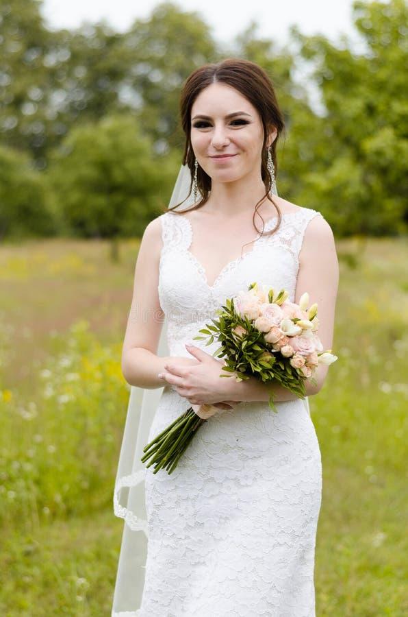 Ein schönes verheiratetes Mädchen im Hochzeitskleid, werfend für ein Fotoschießen in einem belarussischen Dorf auf Grüner Hinterg stockbild