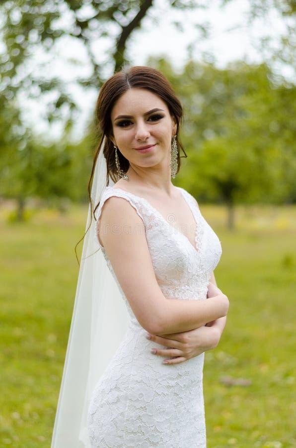 Ein schönes verheiratetes Mädchen im Hochzeitskleid, werfend für ein Fotoschießen in einem belarussischen Dorf auf Grüner Hinterg stockfotos