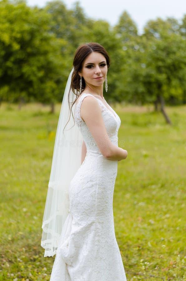 Ein schönes verheiratetes Mädchen im Hochzeitskleid, werfend für ein Fotoschießen in einem belarussischen Dorf auf Grüner Hinterg lizenzfreie stockfotografie