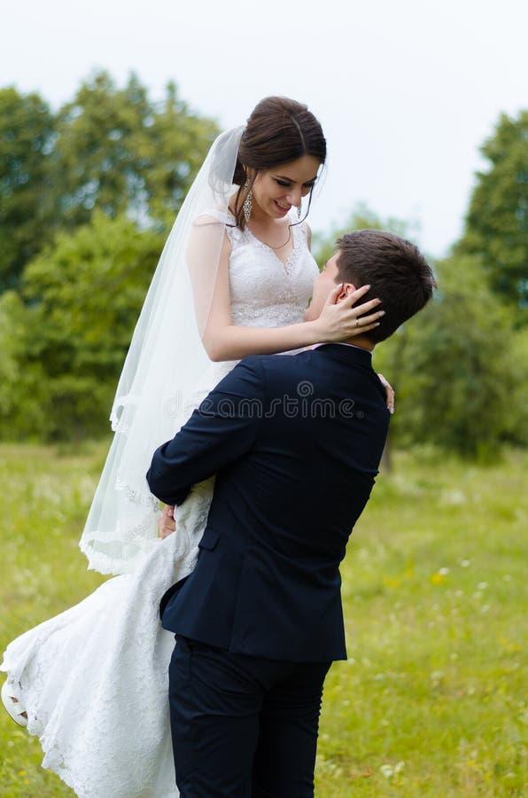 Ein schönes verheiratetes Paar in den Brautkleidern, werfend für ein Fotoschießen in einem belarussischen Dorf auf Grüner Hinterg lizenzfreie stockfotografie