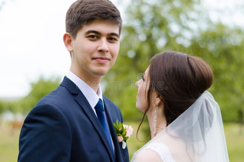 Ein schönes verheiratetes Paar in den Brautkleidern, werfend für ein Fotoschießen in einem belarussischen Dorf auf Grüner Hinterg stockfotos