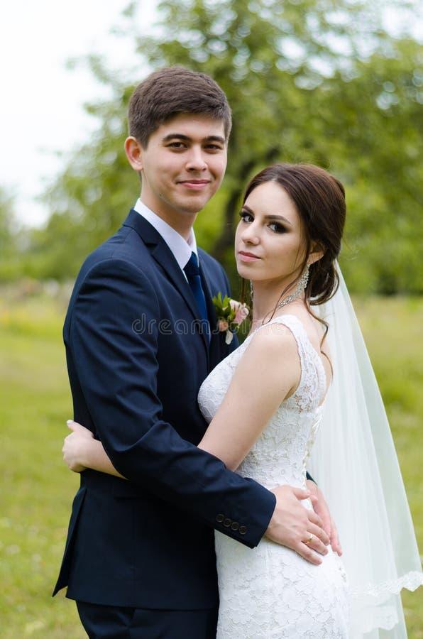 Ein schönes verheiratetes Paar in den Brautkleidern, werfend für ein Fotoschießen in einem belarussischen Dorf auf Grüner Hinterg lizenzfreies stockfoto