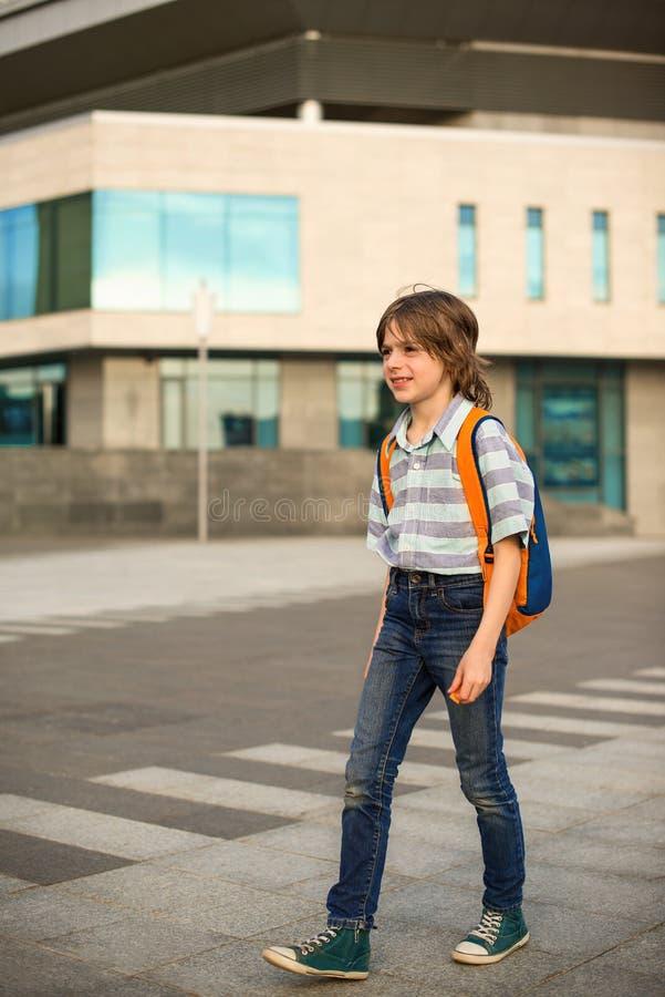 Ein Schüler blond, tragend in einem Hemd und in den Jeans, Wege mit einem kn stockbilder