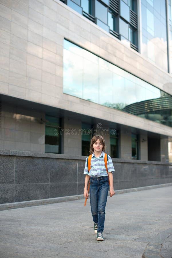 Ein Schüler blond, tragend in einem Hemd und in den Jeans, Wege mit einem kn stockfotografie