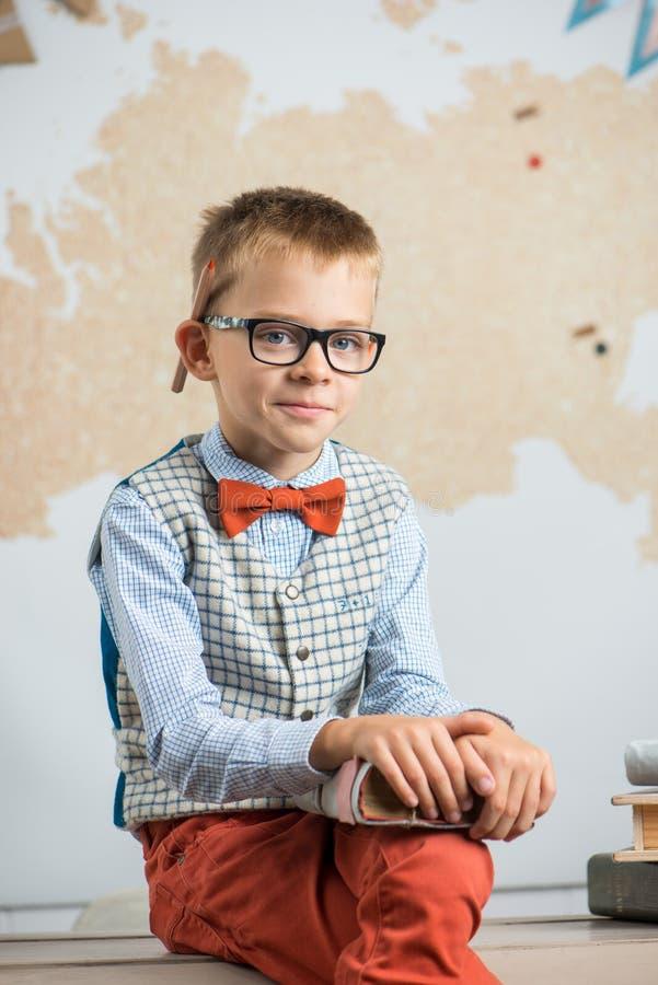 Ein Schüler, der Gläser trägt, sitzt auf einem Schreibtisch und hält ein Buch in seinen Händen stockfotos