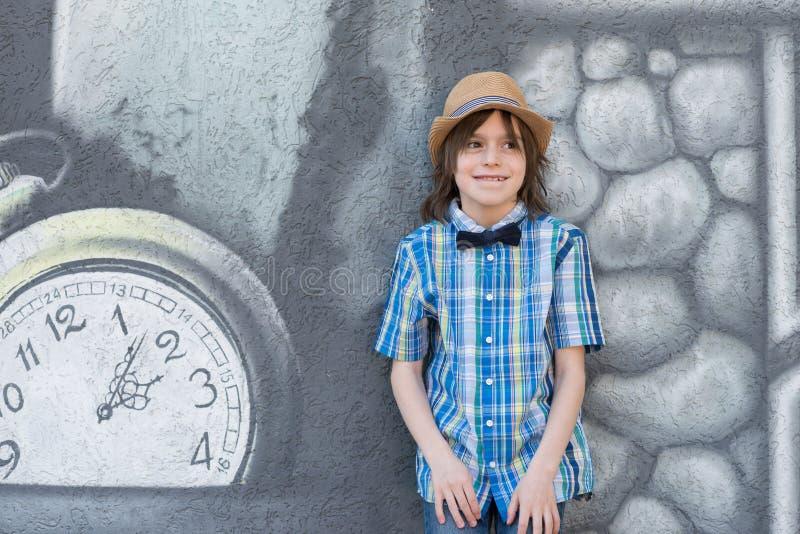 Ein Schüler in einem Hut und in einer Bindung - Schmetterling steht das te bereit stockfoto