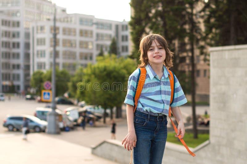 Ein Sch?ler, der, tragend in einem Hemd und in den Jeans, Wege mit einem Rucksack blond ist, geht durch das gro?e alte Geb?ude zu stockfoto