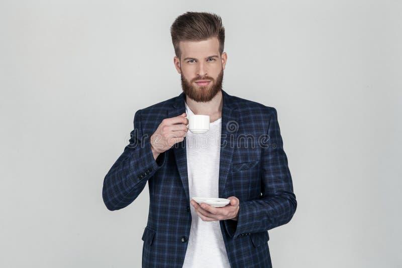 Ein sch?ner sexy b?rtiger Gesch?ftsmann in einer Jacke betrachtet die Kamera einen Tasse Kaffee in seinen H?nden halten, steht er lizenzfreies stockfoto