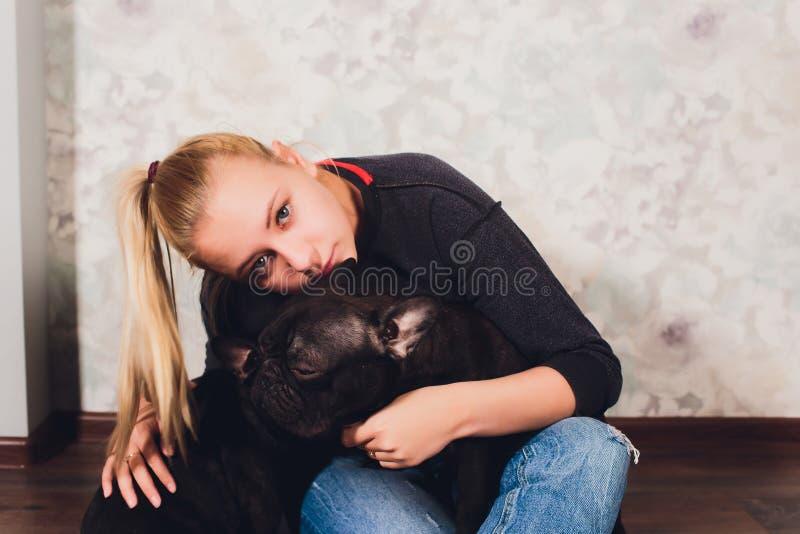 Ein sch?nes junges M?dchen sitzt und h?lt viel kleinen Welpen eines Hundes der franz?sischen Bulldogge stockfotos