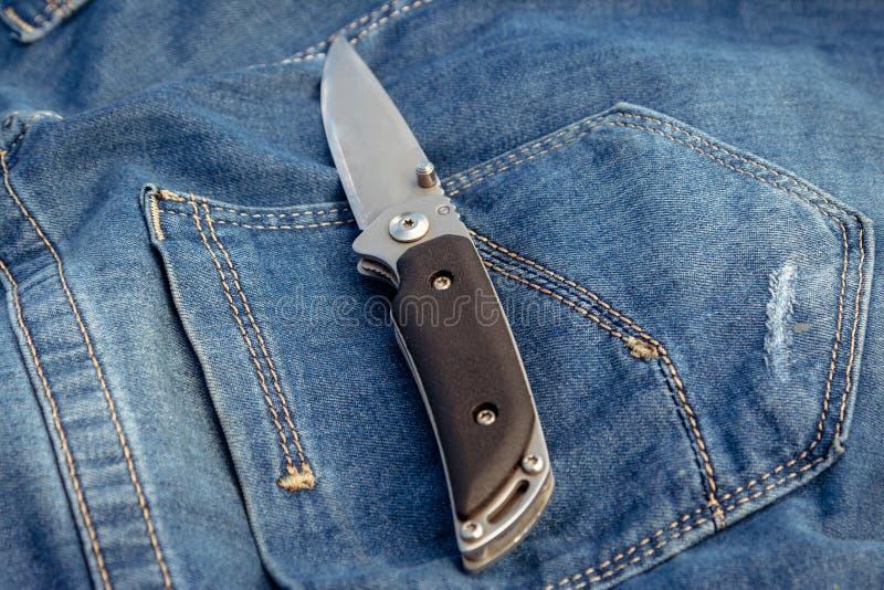 Ein scharfes Messer auf einem Jeanshintergrund in der Natur lizenzfreies stockbild