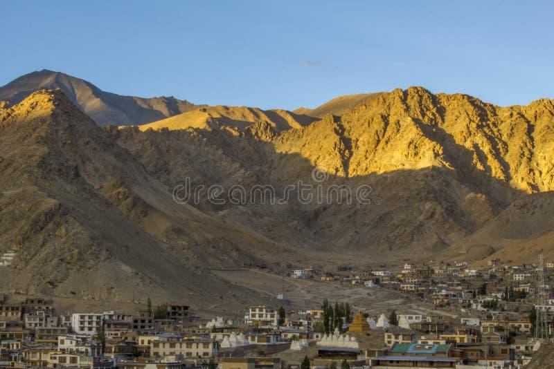 Ein Schatten vom Sonnenuntergang auf dem Berg über der Stadt lizenzfreies stockbild