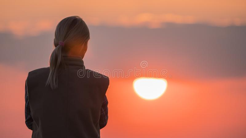 Ein Schattenbild einer Frau, die eine große rote Sonne betrachtet stockbilder