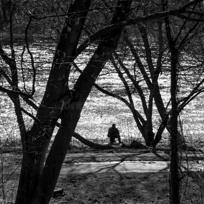 Ein Schattenbild eines alten Mannes, der durch das Flussangeln nahe bei einer Laufbahn sitzt stockbild
