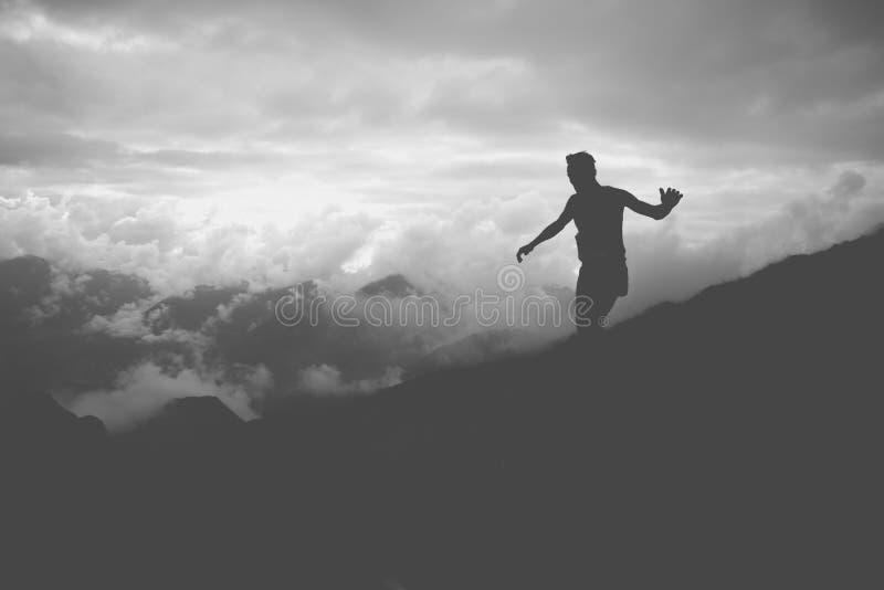 Ein Schattenbild eines Athleten, der hinunter die Steigungen eines Berges l?uft stockfotografie