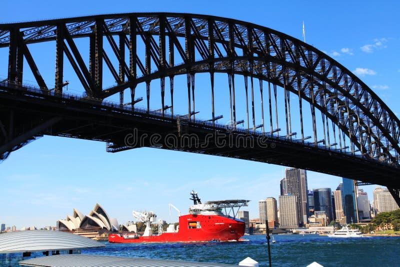 Ein Schiff, das durch Sydney Opera House And Harbour-Brücke überschreitet stockbilder