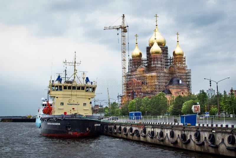 Ein Schiff nahe einem Pier von Fluss Arkhangelsk Severnaya Dvina mit einem Tempel auf Hintergrund stockfotos
