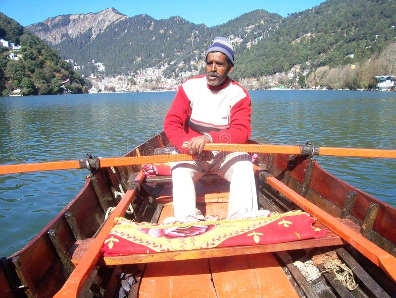 Ein Schiffer, der für Lebensunterhalt am nainital See fährt stockbild
